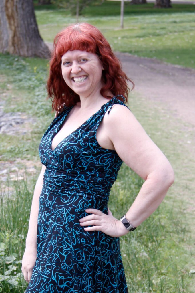 Portrait of person smiling at the camera in an open park near a walking trail. This is Tia Young, the founder of Badass Therapy. She offers ptsd treatment in denver, abuse counseling in colorado, therapy for attachment styles in denver, co, and more. Contact her for alternatives to traditional talk therapy and start healing!