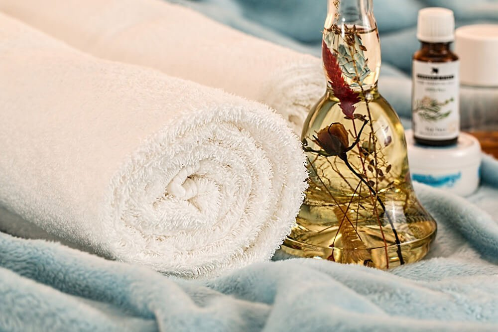Close up of rolled towels resting next to glass vase of essential oils with plants inside. Badass Therapy provides massage therapy, energy healing, alternative therapy, and more. Contact us today for support from an experienced therapist, and remember you're a badass!
