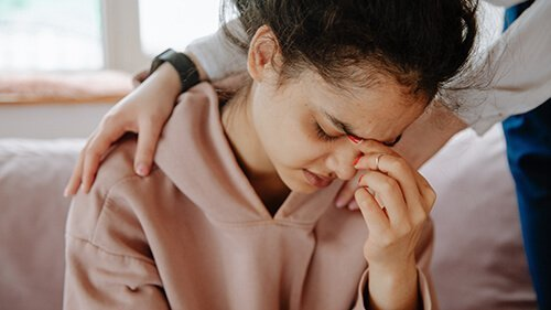 Young woman pinches the bridge of her nose being comforted by hands on her shoulders . She is struggling after experiencing domestic violence and sexual assault. Badass Therapy offers counseling for domestic violence in colorado, abuse counseling in colorado, counseling for domestic violence and sexual assault, and more.
