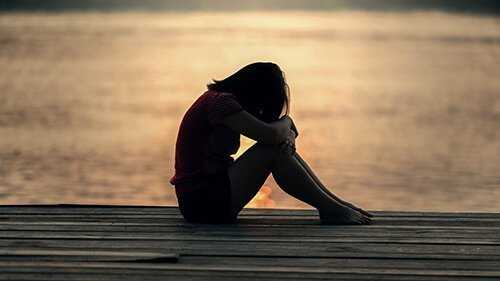 Young woman sits at the end of dock as she remembers the domestic violence from an abusive relationship. Badass Therapy offers counseling for domestic violence in colorado, abuse counseling in colorado, support with sexual assault, and more.