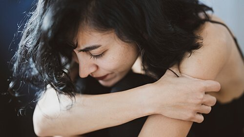Woman holds her arm as she sits hunched over. She is struggling through a memory of sexual assault. Badass Therapy offers abuse counseling in colorado, counseling for domestic violence in colorado, and more. Contact us today for counseling for domestic violence and sexual assault.