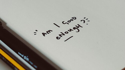 """Close up of a blank sheet of paper with a pen and pencil by its side. In the corner, there is a handwritten question asking """"Am I Good Enough?"""". Badass Therapy knows that you are! We offer grief and loss therapy in denver, online grief therapy in colorado, therapy for attachment issues in denver, co, and more. Contact us today for the support you deserve, and remember you're a badass!"""