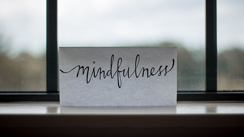 """Close up of notecard on windowsill with """"mindfulness"""" written across the front. Badass Therapy offers complex ptsd treatment in colorado, alternative therapy, massage therapy, energy healing, and more. Contact us today, and start remembering you're a badass!"""