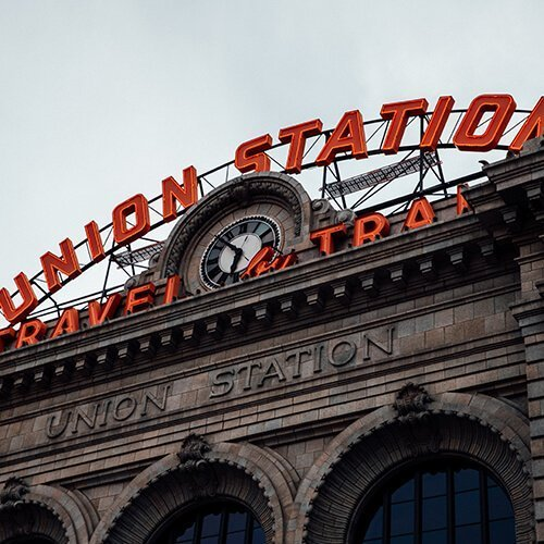"""Close up of the Union Station Sign in Denver. The bright neon lights reading """"union station, travel by train"""" light up against the cloudy overcast sky. Badass Therapy offers grief and loss therapy in Denver, counseling for domestic violence in colorado, developmental trauma therapy in denver, co. Contact her for healing from developmental trauma, alternative therapy, energy healing, and start remembering you're a badass!"""