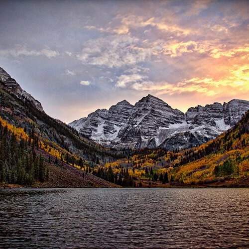 Nature shot of snow dusted mountains as the sun rises behind them. There is also a thick forest of fall leaves, and a large lake. Badass Therapy offers support from an inclusive therapist. We offer abuse counseling in colorado, complex pstd treatment in colorado, therapy for attachment issues in denver, co, and more. Contact us today for the support you deserve, and remember you're a badass!