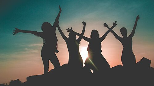 Four women stand with their arms outstretched towards the sky in a relaxed, celebratory stance in the sunset. Badass Therapy can help you feel joy again with trauma therapy in Colorado. We also offer chronic pain therapy, complex ptsd treatment, grief and loss therapy, and more with online therapy in Colorado.