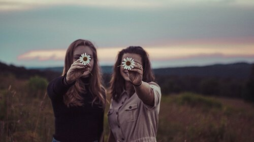 Two women stand in an open field as they hold daisies in front of their smiling faces. They are feeling more hopeful after receiving trauma therapy. Badass Therapy offers trauma therapy in colorado. We also offer grief and loss therapy, complex ptsd treatment, and more. Contact us today for online trauma therapy in colorado.