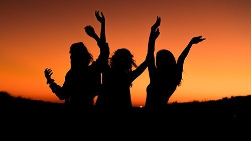 Three women stand with their hands in the air, against the evening sunset. Their silhouettes almost seem joyful as they celebrate their friend recovering from past trauma. Badass Therapy offers trauma therapy in Colorado, chronic pain therapy in Colorado, online trauma therapy in colorado, and more. Contact us today for support with grief and loss therapy, and more.