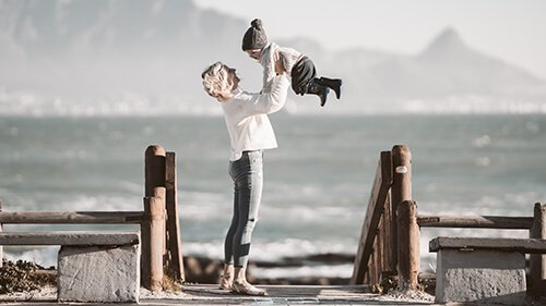 Mother on a wooden pier smiles as she lifts her young child into the air. The child is wearing a beanie, and appears happy. Badass Therapy offers complex ptsd treatment in Colorado, therapy for attachment issues in Denver, CO, childhood trauma therapy in Denver, CO, and more. Contact us today, and begin healing from developmental trauma!