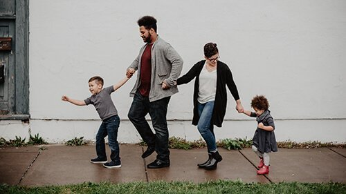 A family of four walks down the slick, wet sidewalk. The young son is leading the way, with his father, mother, and little sister joining hands behind him. Badass Therapy offers childhood trauma therapy in Denver, CO, complex ptsd treatment in Colorado, and more. Contact us today to begin developmental trauma therapy in denver, co