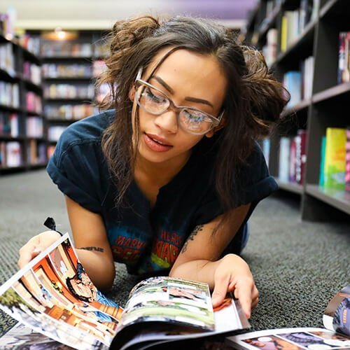College student lays on the ground of a library as she reads a comic book. She has felt more comfortable reading comics after counseling for self-esteem in denver, co. Badass Therapy offers low self-esteem therapy in denver, co, self confidence counseling in denver, co, counseling for self-esteem, and more. Contact us today for the support you deserve.