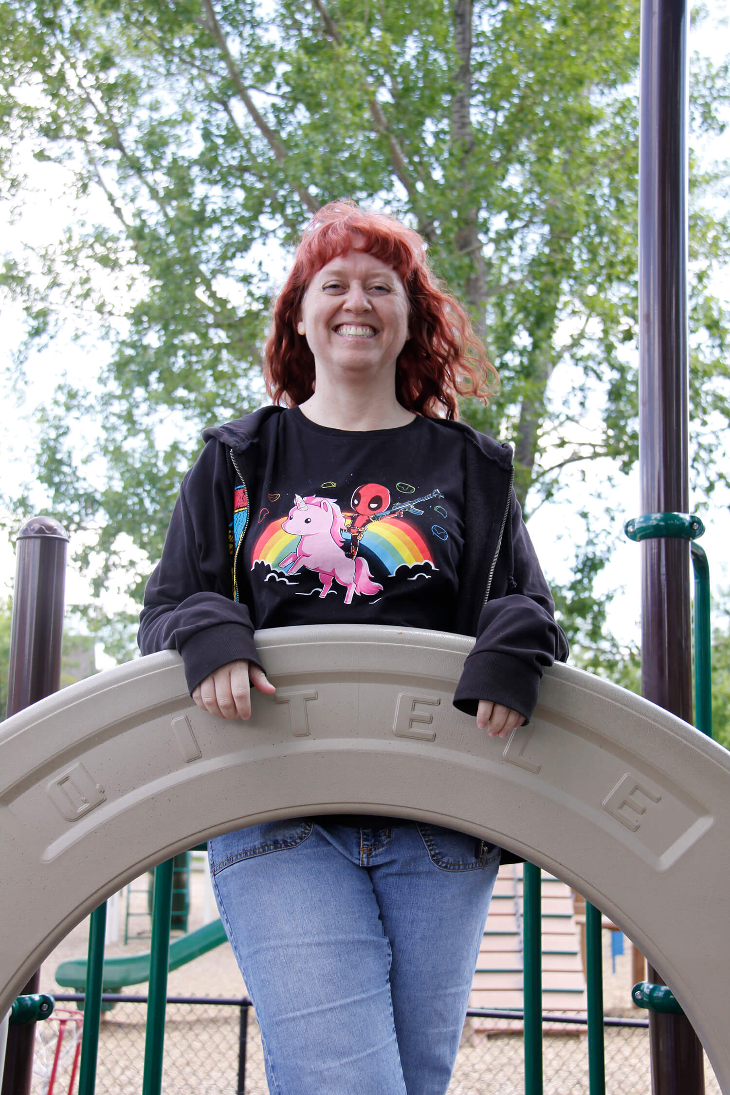 A woman stands with a bright smile as she looks at the camera. She is standing outside, and a park slide can be seen in the background. This is Tia Young, the founder of Badass therapy. She offers childhood trauma therapy in denver, co, complex ptsd treatment in colorado, counseling for domestic violence and rape, and more. Contact her today and start healing!
