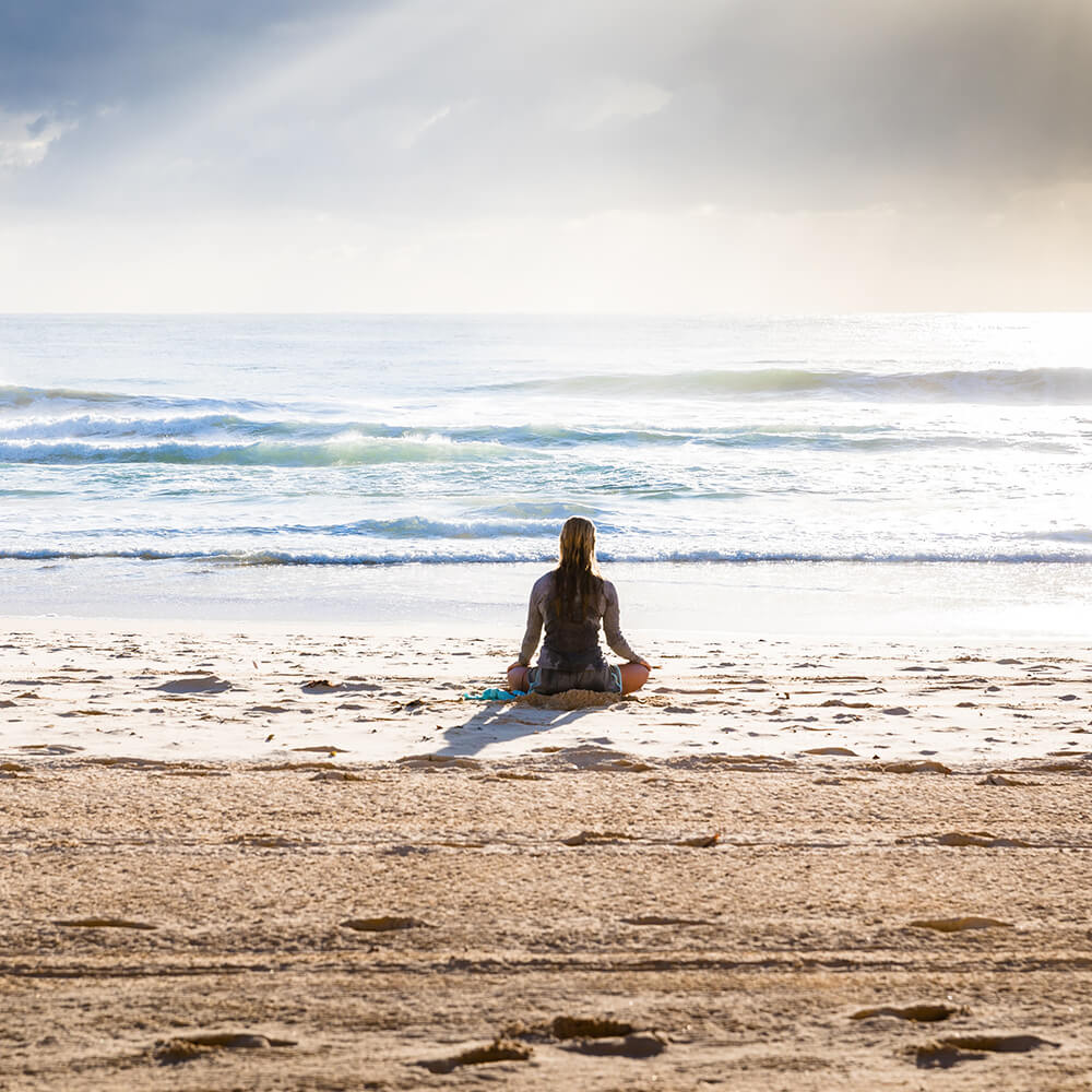 Woman sits on shore as the tide rolls in. She is feeling better after therapy for depression and anxiety in denver, co. Badass Therapy offers therapy for depression in denver, co, online depression counseling, panic attacks, and more. Contact us today to get in touch with a depression therapist today.