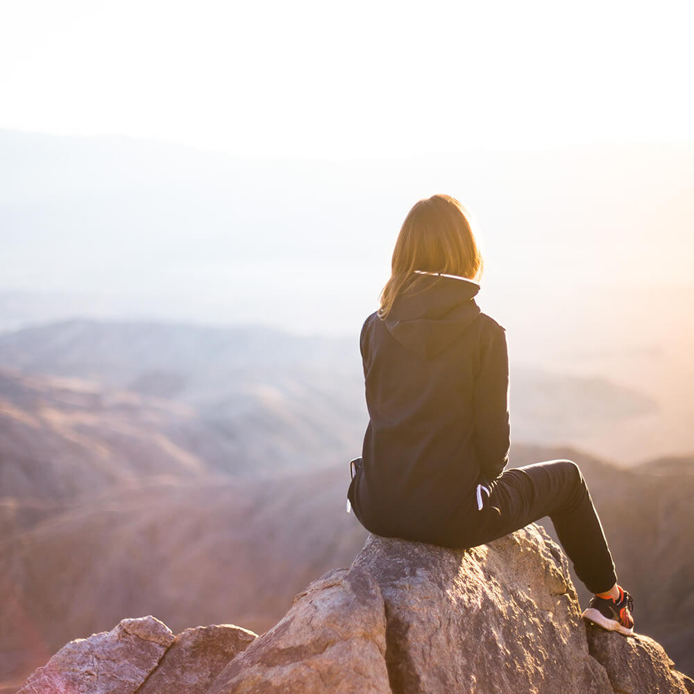 Woman sits on top of a mountain as she looks out over the land below. She is feeling successful after counseling for depression and anxiety. Badass Therapy offers treatment for depression and anxiety in denver, co, online depression counseling, and more. Contact us to start depression therapy today.